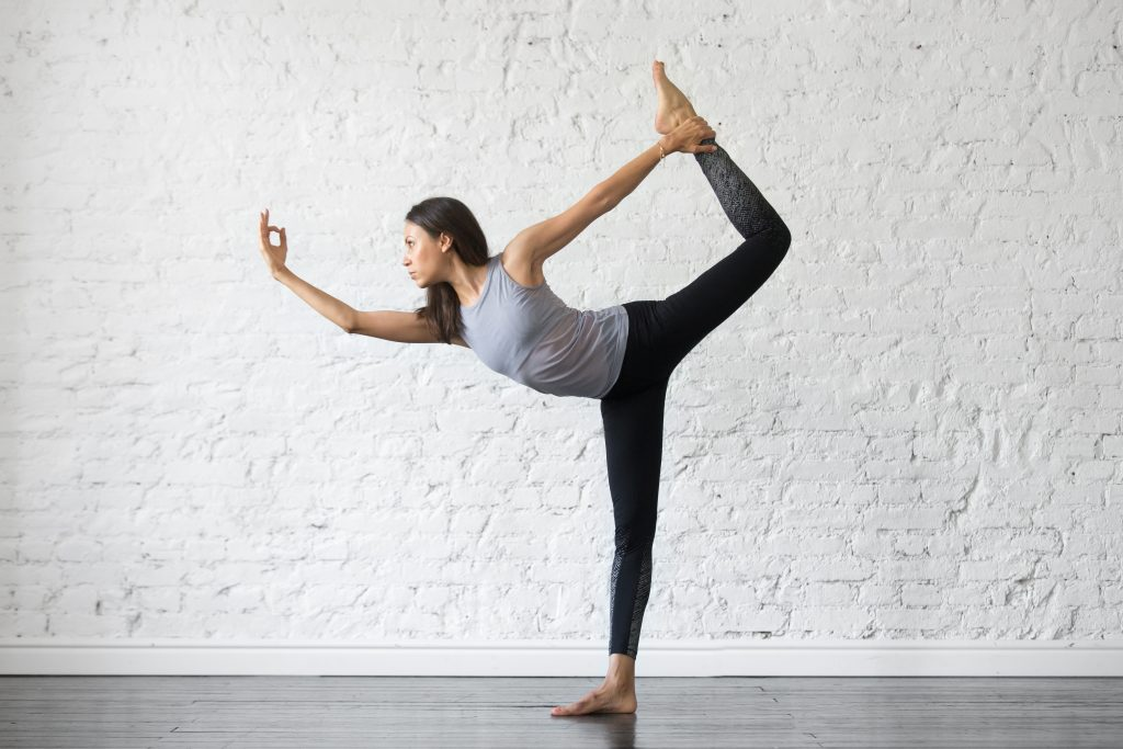 Young attractive woman practicing yoga, stretching in Natarajasana exercise, Lord of the Dance pose, working out, wearing sportswear, gray tank top, black pants, indoor full length, studio background