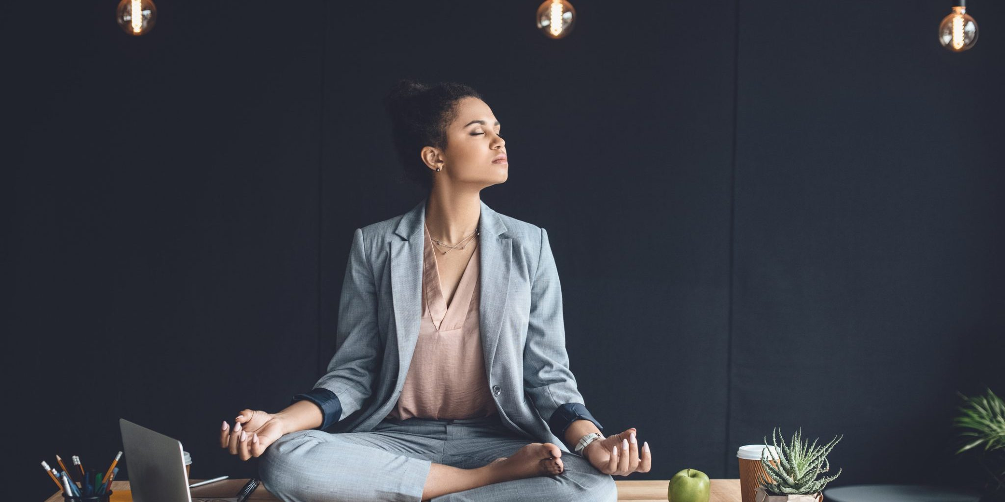 african american businesswoman sitting in lotus pose on table while meditating in office