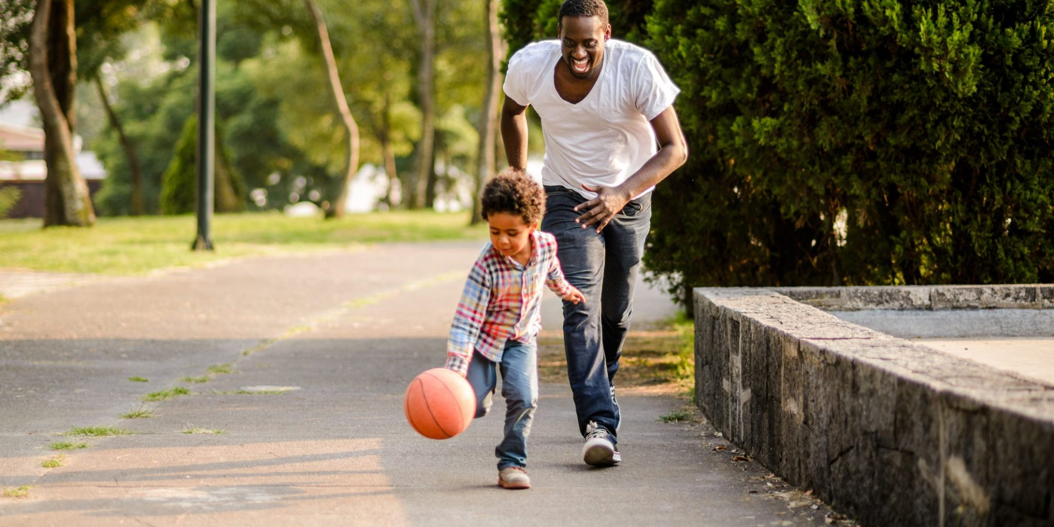Horizontal photo of son and father playing basketball